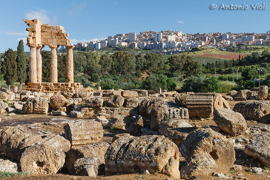 Temple of Castor and Pollux in Valley of the Temples in Agrigento with the city in the background.