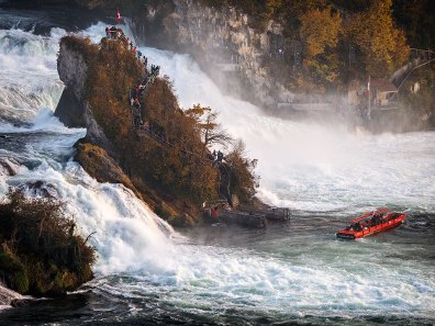 Rhine Falls with viewpoint rock and tourist boat, Neuhausen, Switzerland.