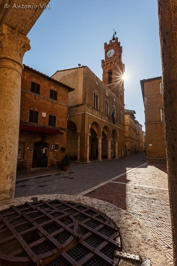 Piazza Pio II and the Palazzo Comunale (Comunal Palace) at sunrise viewed through the ancient well, Pienza, Tuscan