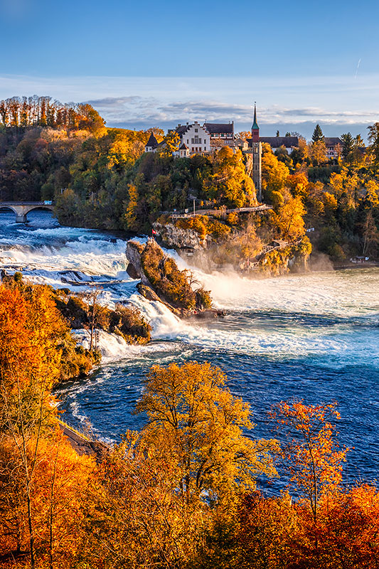 The Rhine Falls with autumn colors and the Laufen Castle in the background.