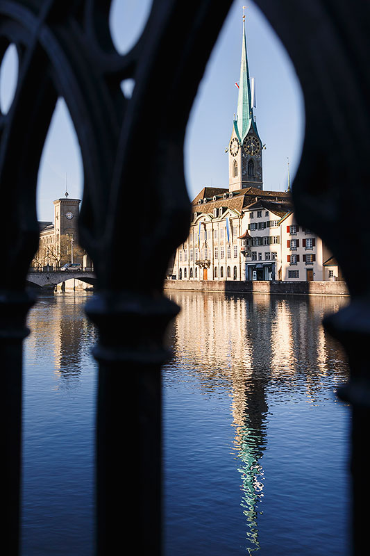 The Fraumunster church, reflected on the Limmat river, seen through the railing.Zurich, Switzerland.