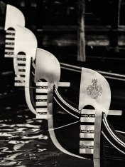 Steel prow-heads of Gondolas moored on San Marco Canal, Venice, Italy.
