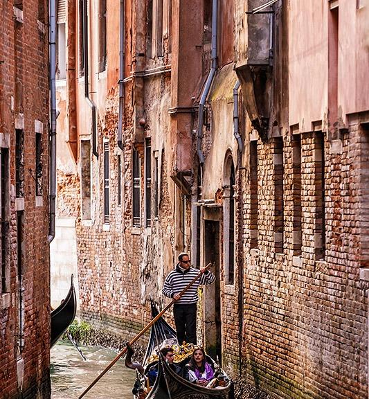 Gondola in a narrow canal in Venice, Italy.