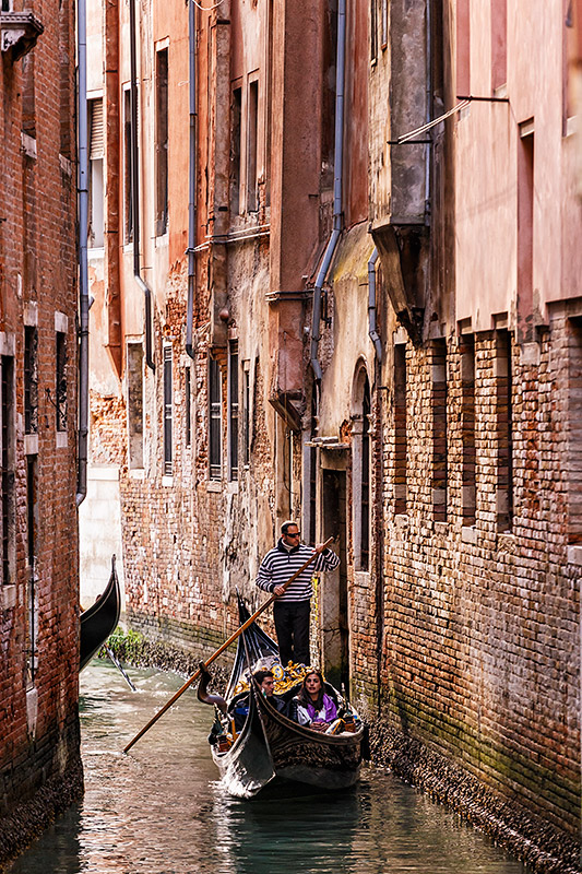 Gondola in a narrow canal in Venice, Italy.