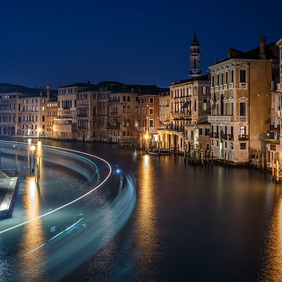 The Grand Canal at night with the light trails of a Vaporetto (waterbus), view from Rialto Bridge, Venice, Italy.