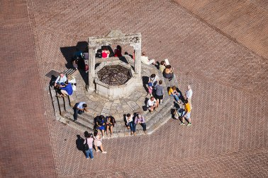 "Aerial view of people sitting around the medieval well in ""Piazza della Cisterna"" in San Gimignano, Tuscany, Italy."