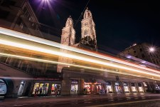 Zurich, the Grossmuenster church at night with light trails left by a tram.