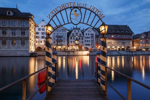 """Pier at """"Hotel zum Storchen"""" and Limmat river at night, Zurich, Switzerland."""
