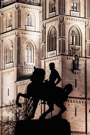 Gothic twin towers of the Grossmunster cathedral with the silhouette of the statue of Mayor Hans Waldmann on horseback, Zurich, Switzerland.
