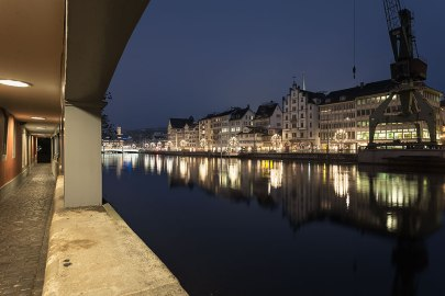 Zurich, old city buildings reflected in the river Limmat seen from a covered walkway.