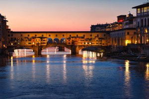 Ponte Vecchio at night reflected on the river Arno, Florence, Tuscany, Italy.