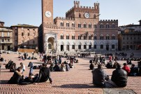 Tourists relaxing in Piazza del Campo square, Siena, Tuscany, Italy.