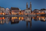 The old town of Zurich with the church Grossmunster reflected on the river Limmat at dusk, Switzerland.