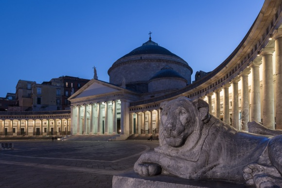 Church of San Francesco di Paola on Piazza del Plebiscito square with floodlights with the lion statue in the foreground, Naples, Italy.