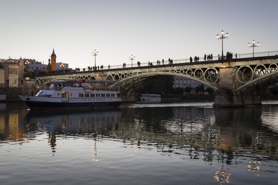 Triana Bridge and Guadalquivir river at dusk in Seville.