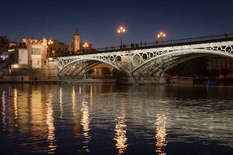 Triana Bridge and Guadalquivir river at night in Seville.