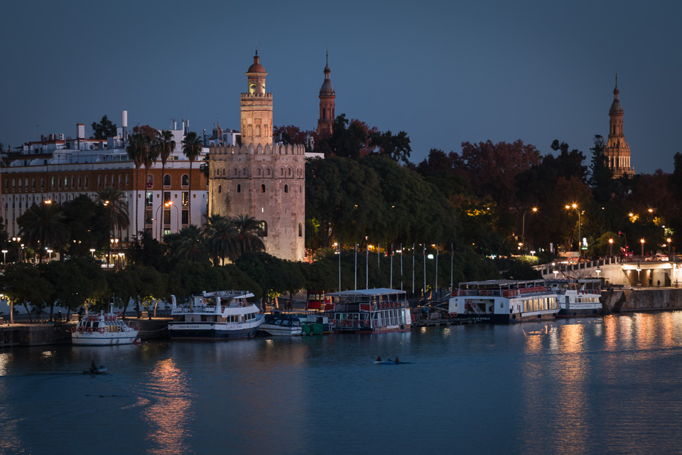 Torre del Oro and Guadalquivir river at night in Seville.