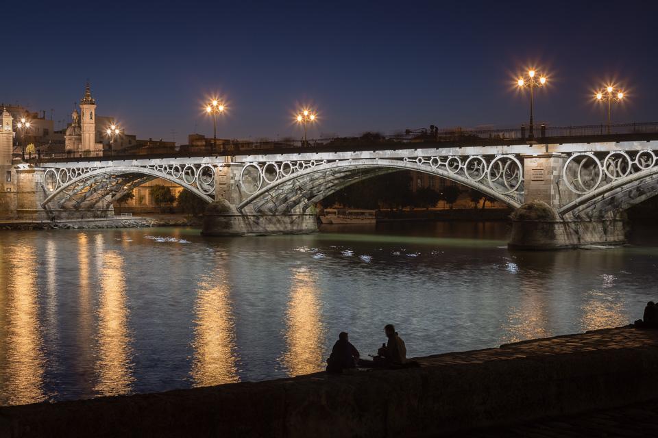 Triana Bridge and Guadalquivir river at night in Seville.