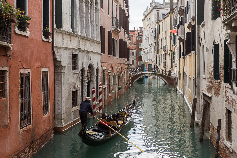 Gondolier with tourists in a canal in Venice, Italy