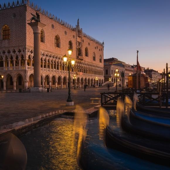 Doge's Palace at dawn with gondolas mooring at Riva degli Schiavoni, Venice, Italy