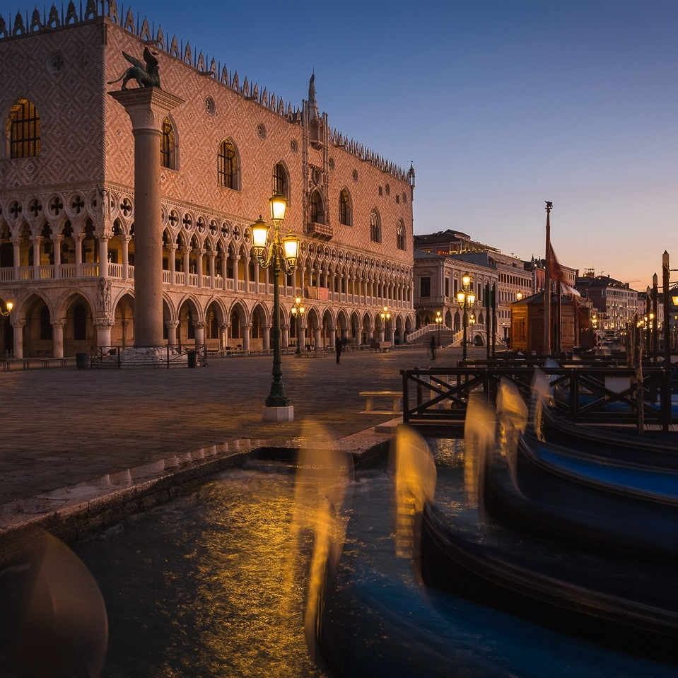 Doge's Palace at dawn with gondolas mooring at Riva degli Schiavoni, Venice, Italy