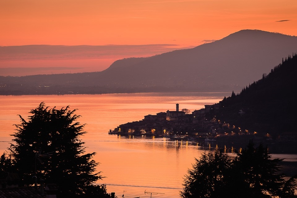 Lake Iseo with the town of Peschiera Maraglio on Monte Isola at dusk, Lombardy, Italy